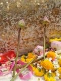 Sakral spirande lotusblomma och den färgglade girlanden på Buddha skulpterar med bladguldbakgrund Fotografering för Bildbyråer