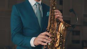 Saksofonista w błękitnym kostiumu bawić się na złotym saksofonie przy sceną elegancja jazzes zdjęcie wideo