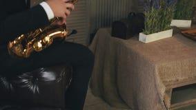 Saksofonista w kurtki obsiadaniu na krześle z złotym saksofonem jazzes Stoi Up zdjęcie wideo
