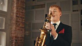 Saksofonista w obiadowej kurtce stoi up na scenie z złotym saksofonem jazzes zdjęcie wideo