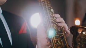 Saksofonista w obiadowej kurtce wykonuje na scenie Światło saksofon, złoty jazzes zdjęcie wideo