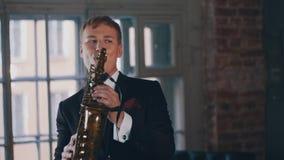Saksofonista w obiadowej kurtki sztuce na złotym saksofonie Żywy występ jazzes zbiory