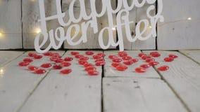 Sakta lutande som skjutas av lyckligt någonsin efter tecken med röda hjärtor omkring och ljus, röd baloon på bakgrund red steg