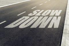 Sakta ner hastighetsbegränsningtecken på huvudvägen Royaltyfri Bild
