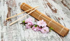 Sakura branch and sticks on a bamboo mat Stock Images