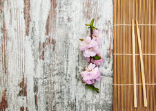 Sakura branch and sticks on a bamboo mat Royalty Free Stock Images
