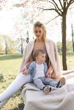 SAKURA Cherry Blossom - Young mom mother sitting with her little boy baby son in a park in Riga, Latvia Europe stock images