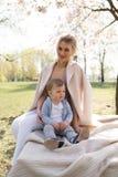 Sakura k?rsb?rsr?d blomning - den unga mammamodern som sitter med hennes pys, behandla som ett barn sonen i parkerar i Riga, Lett arkivbild