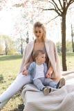 Sakura k?rsb?rsr?d blomning - den unga mammamodern som sitter med hennes pys, behandla som ett barn sonen i parkerar i Riga, Lett arkivbilder