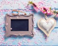 Sakura pica las flores, el corazón decorativo y la pizarra vacía encendido Fotos de archivo