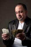 Salário de dinheiro obscuro Fotografia de Stock