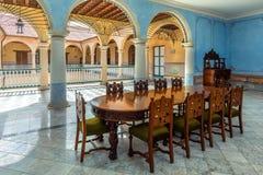 Salão azul com colunas, marrom, a tabela de madeira e as cadeiras cinzeladas dentro fotografia de stock royalty free