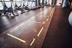 Salão com inventário dos esportes e equipamento em um fitness center vazio imagem de stock royalty free