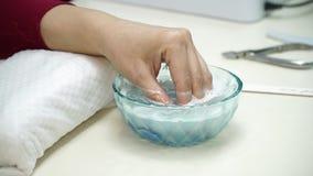 Salão de beleza do tratamento de mãos O manicuro faz o procedimento para o cuidado dos pregos prego hidratando do procedimento, m filme