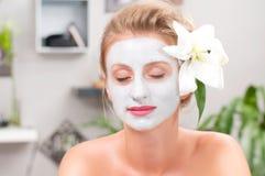 Salão de beleza dos termas Mulher bonita com máscara facial da argila no salão de beleza fotos de stock royalty free