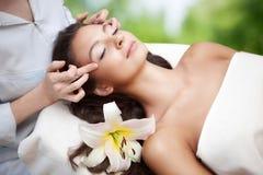 Salão de beleza dos termas: Mulher bonita nova que tem a massagem facial Foto de Stock Royalty Free