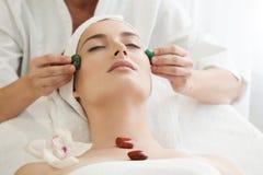 Salão de beleza dos termas: Mulher bonita nova que tem a massagem facial com Ston Fotos de Stock Royalty Free