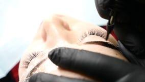 Salão de beleza de beleza Feche acima do esteticista masculino nas luvas pretas que fazem o procedimento permanente da composição filme