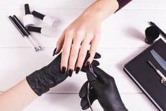 Salão de beleza de beleza Tratamento de mãos preto de fatura mestre em luvas pretas Fundo branco salon imagens de stock royalty free