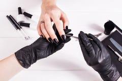 Salão de beleza de beleza Tratamento de mãos preto de fatura mestre em luvas pretas Fundo branco salon imagens de stock