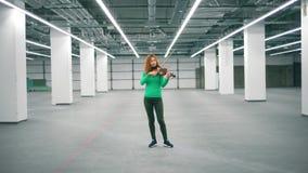 Salão espaçoso com um violinista fêmea que joga o instrumento filme