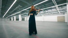 Salão vazio e uma mulher que joga o violino ao andar video estoque