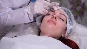 Salón de belleza acogedor Maquillaje permanente del procedimiento En el sofá el cosmetólogo paciente pone la pintura en sus cejas almacen de metraje de vídeo