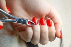 Salón de belleza, aplicación de la manicura, cortando la cutícula con las tijeras imagenes de archivo