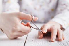Salón de belleza, aplicación de la manicura, cortando la cutícula con scisso Fotografía de archivo libre de regalías