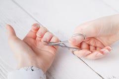 Salón de belleza, aplicación de la manicura, cortando la cutícula con scisso Fotos de archivo