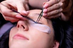 Salón de belleza, cierre del procedimiento de la extensión de la pestaña para arriba Mujer hermosa con el pelo largo imagen de archivo libre de regalías