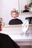 Salón de belleza rubio feliz alegre del peluquero de los rodillos de los bigudíes de pelo de la muchacha Fotos de archivo libres de regalías