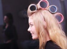 Salón de belleza rubio hermoso del peluquero de los rodillos de los bigudíes de pelo de la muchacha Fotos de archivo libres de regalías