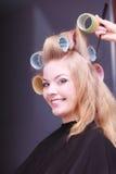 Salón de belleza sonriente rubio hermoso del peluquero de los rodillos de los bigudíes de pelo de la muchacha Fotografía de archivo libre de regalías