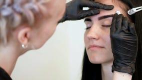 Salón de la belleza el cosmetologist, en guantes de goma negros, limpia suavemente sus cejas con un disco del algodón, cojín de a almacen de metraje de vídeo