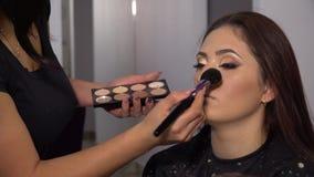Salón de la belleza El modelo hermoso joven de la muchacha se está sentando en la silla El artista de maquillaje hace maquillaje  almacen de video