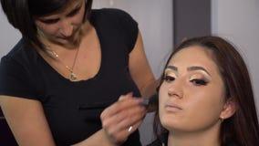 Salón de la belleza El modelo hermoso joven de la muchacha se está sentando en la silla El artista de maquillaje hace maquillaje  almacen de metraje de vídeo