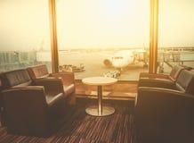 Salón de la salida en el aeropuerto con el asiento y la tabla con los aviones que se preparan para el vuelo fotos de archivo