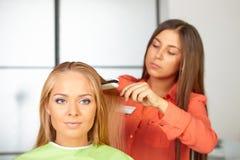 Salón de pelo. Corte de pelo para mujer. Uso de la enderezadora. Imágenes de archivo libres de regalías