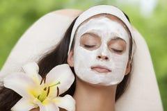 Salón del balneario: Mujer hermosa joven que tiene masaje facial fotografía de archivo