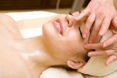 Salón del balneario: Mujer joven hermosa que tiene masaje imagenes de archivo
