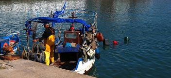 Salónica, Grecia - 21 de abril de 2018: Pescador que consigue listo para pescar con su barco de pesca en el Mar Egeo fotografía de archivo