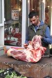 SALÓNICA - GRECIA SEPTIEMBRE 25,2018: La vieja área de mercado, hombre en la madera al aire libre de la carnicería corta la carne imagen de archivo libre de regalías
