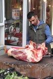 SALÓNICA - GRECIA SEPTIEMBRE 25,2018: La vieja área de mercado, hombre en la madera al aire libre de la carnicería corta la carne foto de archivo