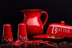 A sal-adega, a pimenta-caixa, a manteiga e o jarro vermelhos ajustaram-se no fundo escuro por Cristina Arpentina Fotos de Stock