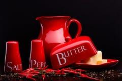 A sal-adega, a pimenta-caixa, a manteiga e o jarro vermelhos ajustaram-se no fundo escuro por Cristina Arpentina Fotos de Stock Royalty Free