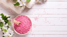 Sal cor-de-rosa do mar na bacia, nas toalhas e nas flores no backg de madeira branco Fotos de Stock Royalty Free