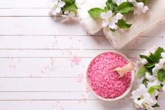 Sal cor-de-rosa do mar na bacia, nas toalhas e nas flores no backg de madeira branco Foto de Stock