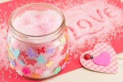 Sal de baño en un tarro al lado de un corazón rosado de la tela escocesa Imagen de archivo