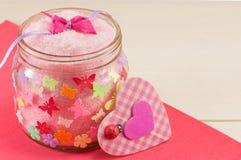 Sal de baño en un tarro al lado de un corazón rosado de la tela escocesa Imágenes de archivo libres de regalías